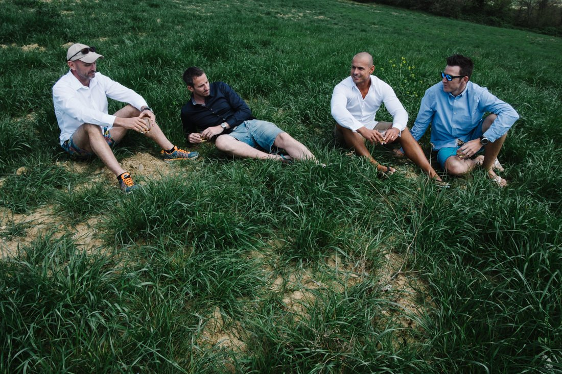 Destination wedding photographer in Pienza. Groom and his groomsmen on green lawn