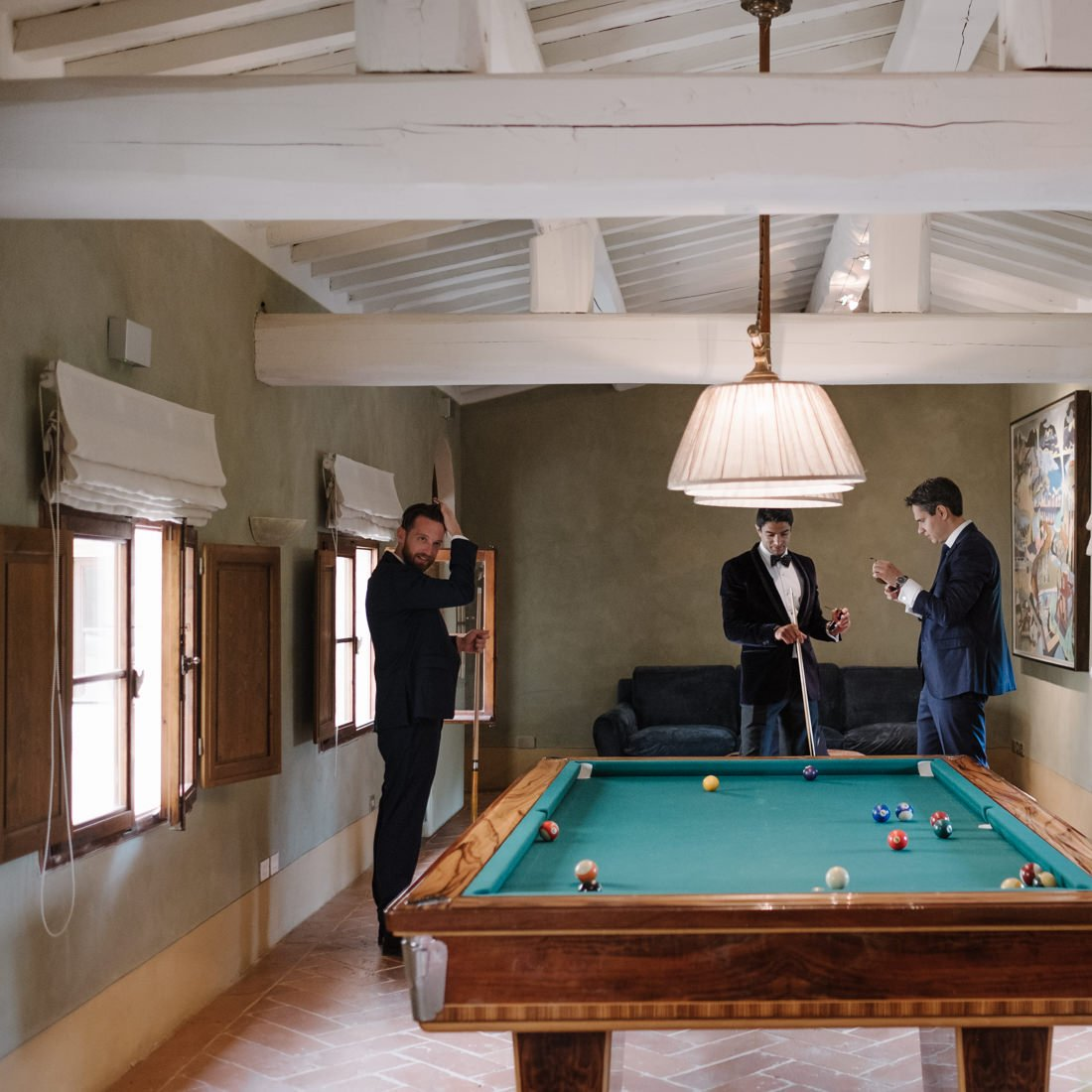 Tuscany destination wedding. Groom and his friends playing billiards
